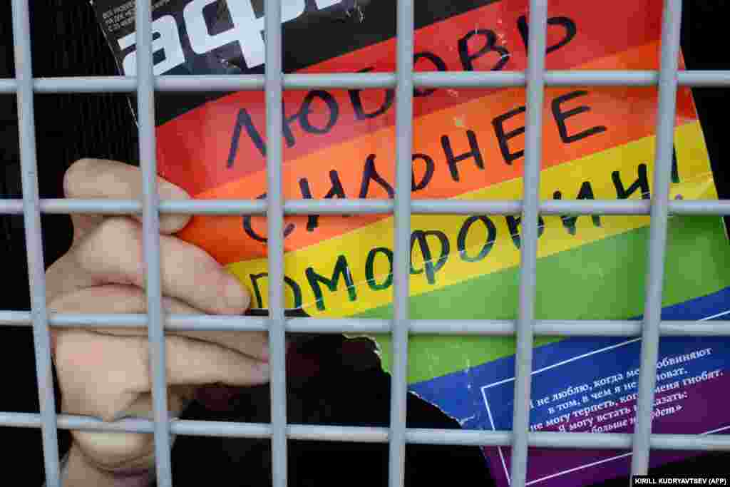 "A Russian gay-rights activist holds a poster reading ""Love Is Stronger Than Homophobia!"" while sitting inside a police van after his detention during an unauthorized gay-rights rally in central Moscow on May 25, 2013."