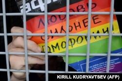 """Шеру кезінде полиция тұтқындаған гей-белсенді """"Гомофобиядан махаббат күшті!"""" деген жазуды полиция көлігінен көрсетіп тұр. Мәскеу, 25 мамыр 2013 жыл."""