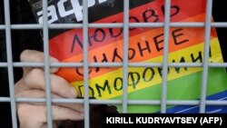 "A gay-rights activist holds a poster reading ""Love is stronger than homophobia!"" while siting inside a police van after his detention during an unauthorized rally in central Moscow in May."