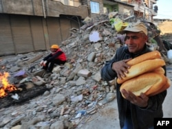 A man carries loaves of bread as a rescue worker takes a break amid buildings damaged in the earthquake in Van.