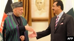 Pakistani Prime Minister Yusuf Raza Gilani (right) greets Afghan President Hamid Karzai at the Prime Minister's House in Islamabad.