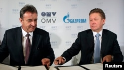 OMV CEO Gerhard Roiss (left) and Gazprom CEO Aleksei Miller sign the final deal to build a branch of the South Stream gas pipeline ending in Austria, in Vienna on June 24.