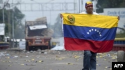 A demonstrator holds a Venezuelan flag on the bridge in Urena, Venezuela, on the border with Colombia.