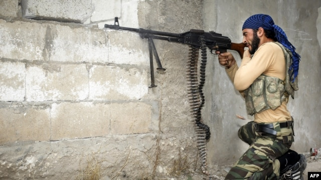 A rebel fighter fires his machine gun at Syrian government troops at the citadel in the town of Harem on October 31.