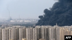 A thick plume of smoke rises above an oil refinery west of the flashpoint city of Homs in early December.