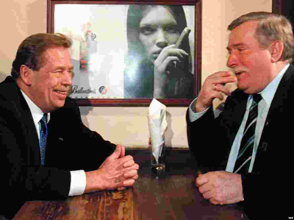 Czech President Havel (left) and former Polish President Lech Walesa joke in a Warsaw pub in March 1998.