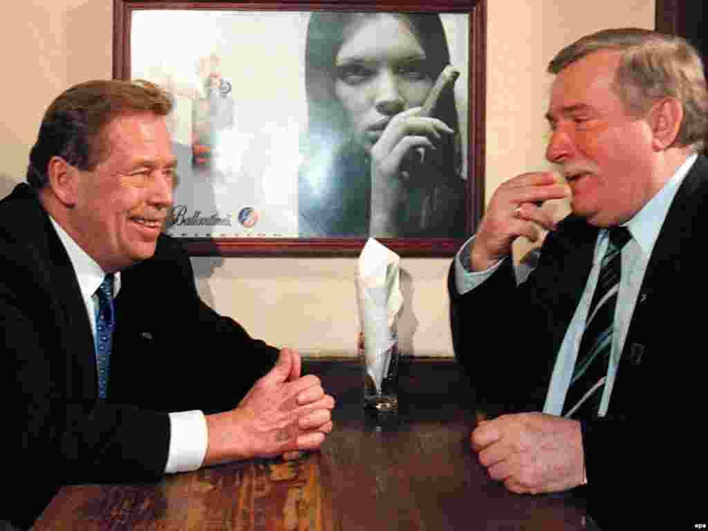 Czech President Havel (left) and former Polish President Lech Walesa joke in a Warsaw pub in March 1998.