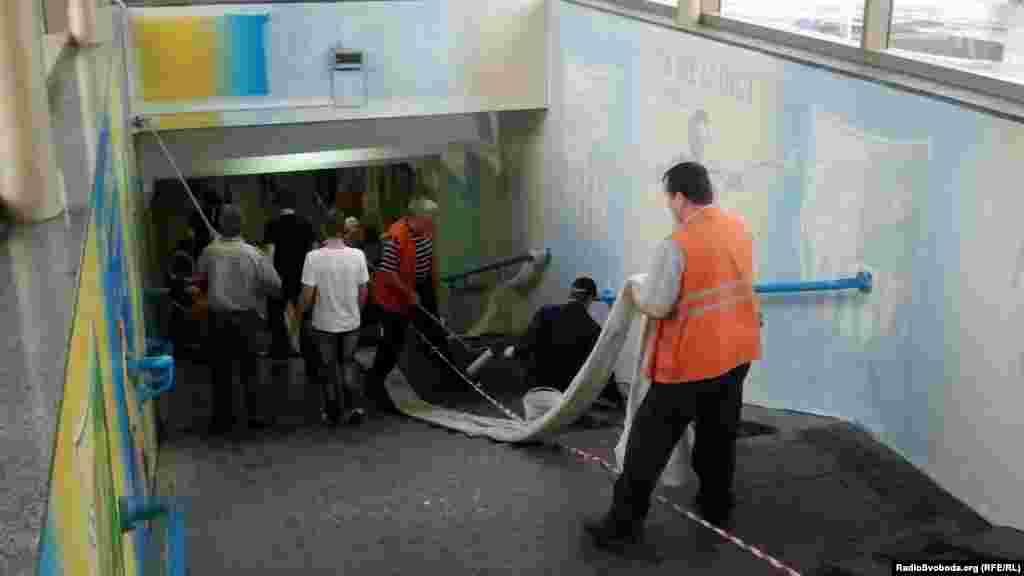 При вході до станції метро «Спортивна» робітники перефарбовують стіни