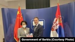 Синиша Мали, српски министер за финансии, ѝ го дава на Чен Бо, кинеска амбасадорка во Србија, планот на српската влада за соработка меѓу Србија и Кина до 2025 година, Белград, 2 јули 2021 година.