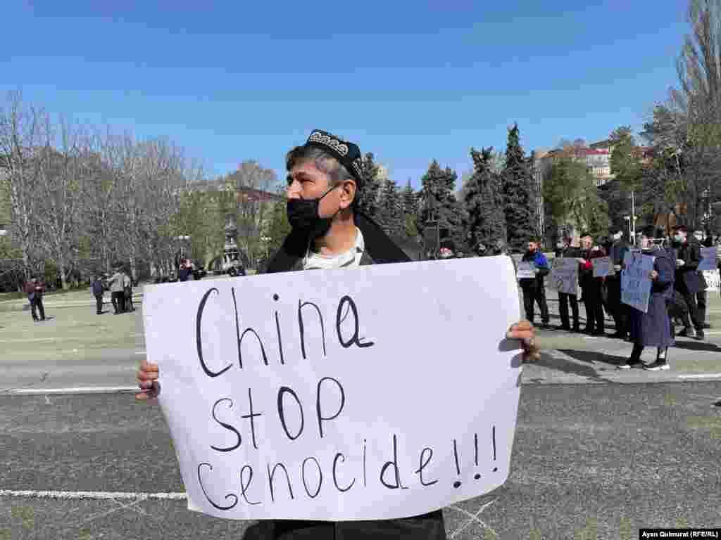 """""""Қытай, геноцидті тоқтат!"""" деген жазуы бар плакат ұстап тұрған белсенді Марат Құрбанов. Ол бірнеше жылдан бері Шыңжаңда із-түзсіз жоғалған туыстарын іздеп, Қытай билігінен ақпарат талап етіп келеді."""