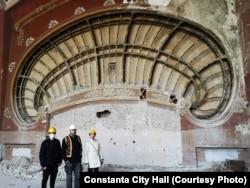 Az építész Radu Cornescu, Apollon Cristodulo, ésLaura Voicila a fal előtt, melyben megtalálták a feljegyzést.