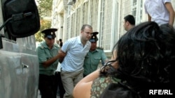 Blogger Emin Milli being taken into court