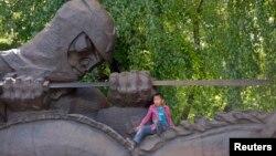 Мальчик сидит на памятнике в день празднования победы во Второй мировой войне. Алматы, 9 мая 2013 года.
