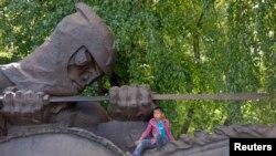 Екінші дүниежүзілік соғыстағы Жеңіс күні ескерткіш үстінде отырған бала. Aлматы, 9 мамыр 2013.