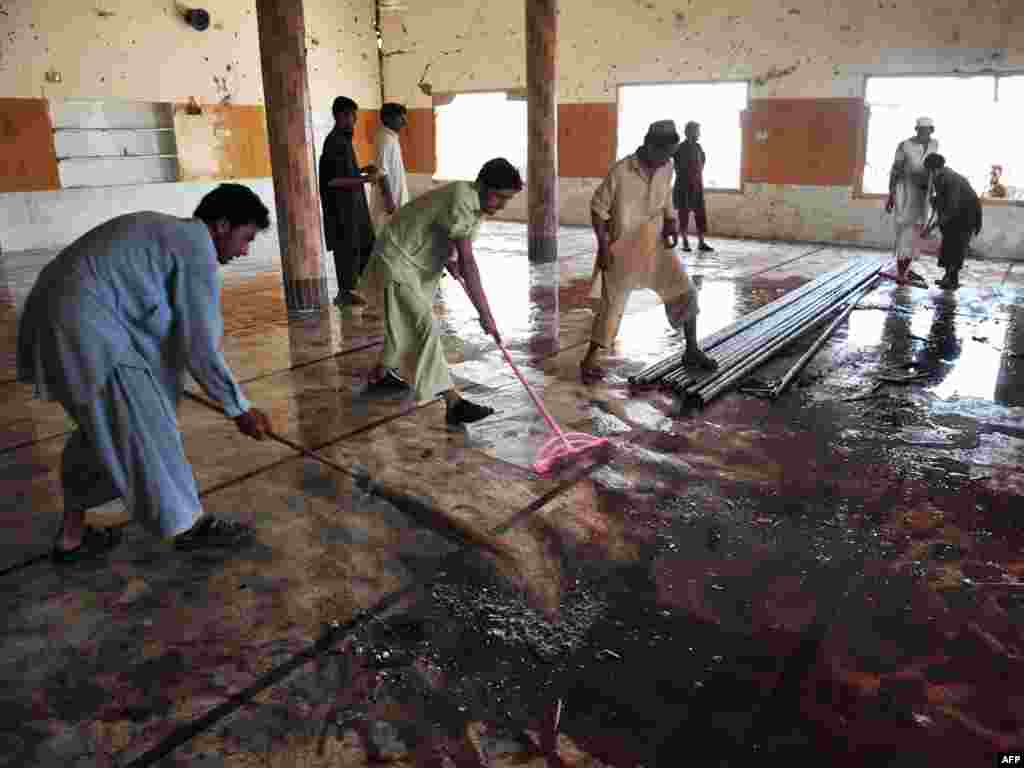 Local residents clean a mosque after a suicide bomb attack in the town of Jamrud, 25 kilometers from Peshawar. A suicide bomber hit a Pakistani mosque during Friday Prayers, killing at least 43 people and wounding more than 100 others.Photo by A. Majeed for AFP