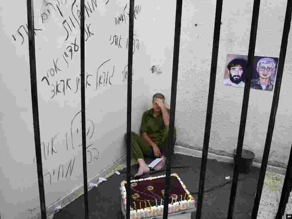 A Palestinian sits in a mock prison cell as he plays the role of missing Israeli soldier Gilad Shalit to mark the fifth anniversary of his capture by Palestinian militants, underneath pictures representing Gilad Schalit (right) and Ron Arad (left), an Israeli airman who disappeared shortly after his plane crashed in Lebanon in 1986.Photo by Hatem Moussa for The AP