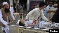People help injured victims get to the hospital after the blast in Darra Adam Khel