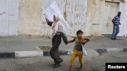 Газа -- Кызын жетелеген палестиналык аял Израиль аскерлеринин операциясы учурунда колуна ак байрак көтөрүп үйүнөн качып баратат 24-июль, 2014.