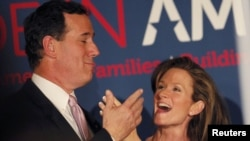 Republican presidential hopeful Senator Rick Santorum celebrates with his wife Karen after winning primaries in Alabama and Mississippi.
