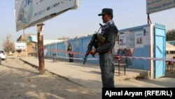 FILE: A police officer stands guard in front of a voting center in the northern province of Kunduz.