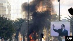 Очаги возгорания на улицах города вследствие столкновений между полицией и демонстрантами. Тунис, 14 января 2011 года.