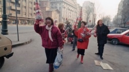 ROMANIA -- Joyfull Romanian woman walking the streets of Bucharest with Christmas decorations, December 25, 1989