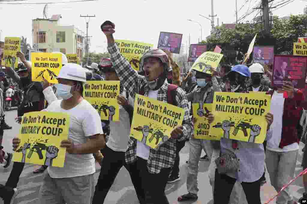 """За време на маршот во Мандалај, Мјанмар на 14 март 2021 година, демонстрантите против пучот имаат натписи на кои пишува: """"Не прифаќаме воен удар""""."""