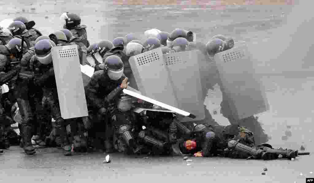 Riot policemen shield themselves during clashes with opposition protesters.