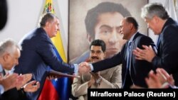 Šef ruske državne naftne kompanije Rosneft, Igor Sečin, (lijevo) rukuje se s venecuelanskim ministrom nafte i predsjednikom državne naftne kompanije južnoameričke države PDVSA, Manuelom Kuevedom, ispred venecuelanskog predsjednika Nikolasa Madura u Maiketijiu decembru 2017.