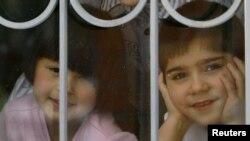 Воспитанники детского дома смотрят через окно. Иллюстративное фото.