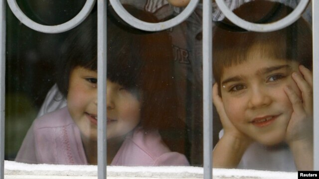 Children look out a window at an orphanage in the southern city of Rostov-na-Donu.