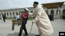 An Uzbek boy carries a chair as he assists an elderly believer to get to a mosque for Friday prayers in Tashkent.