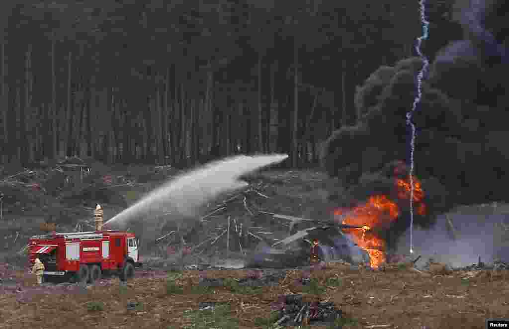 A firetruck sprays water on the wreckage of a crashed Mi-28 helicopter in which one pilot was killed on August 2 near Ryazan, Russia. (Reuters)