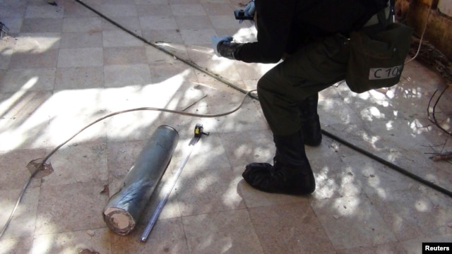 A UN chemical weapons expert gathers evidence at one of the sites of an alleged poison-gas attack in the southwestern Damascus suburb of Moadamyeh on August 26.