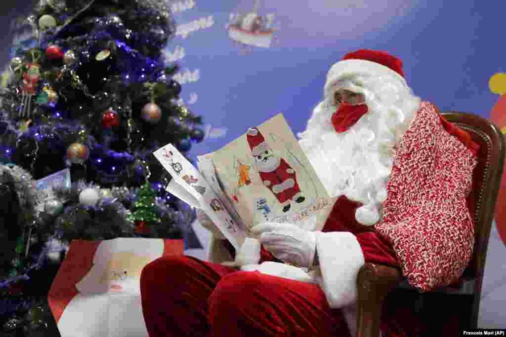 Почтальон в костюме Санта-Клауса читает письма, адресованные Пэр-Ноэлю (французский «Дедушка Рождества»), украшенные сердечками, наклейками и блестками, в Либурне, юго-запад Франции, 23 ноября 2020 года