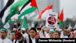 A protester in Jakarta holds up a sign during a rally to condemn U.S. President Donald Trump's decision to recognize Jerusalem as Israel's capital on December 17.