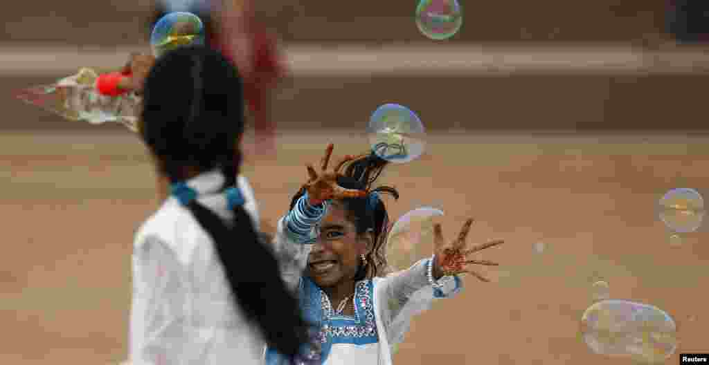 Girls play with bubbles as they celebrate the Eid al-Fitr festival marking the end of Ramadan, the holiest month in the Islamic calendar, at Galle Face Green in Colombo, Sri Lanka. (Reuters/Dinuka Liyanawatte)
