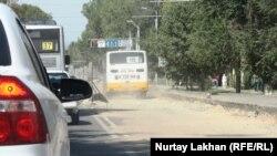 Машины едут по улице, на которой после замены линии подземных коммуникаций не уложили асфальт. Алматы, 5 сентября 2013 года.