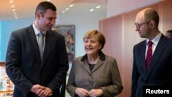 Анґела Меркель (с) під час розмови з Віталієм Кличком (л) і Арсенієм Яценюком (п), Берлін, 17 лютого 2014 року