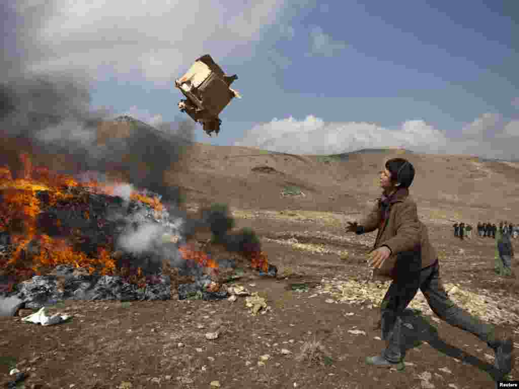 An Afghan boy throws a box on a burning pile of confiscated narcotics in Kabul. - Photo by Ahmad Masood for Reuters