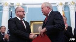 Министр иностранных дел Черногории Срджан Даманович (слева) передает документ о присоединении к НАТО заместителю госсекретаря США по политическим делам Томасу Шэннону, Вашингтон, 5 июня 2017 года.