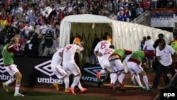 Албанские игроки убегают с поля во время беспорядков в ходе отборочного матча чемпионата Европы с Сербией. Белград, 14 октября 2014 года.