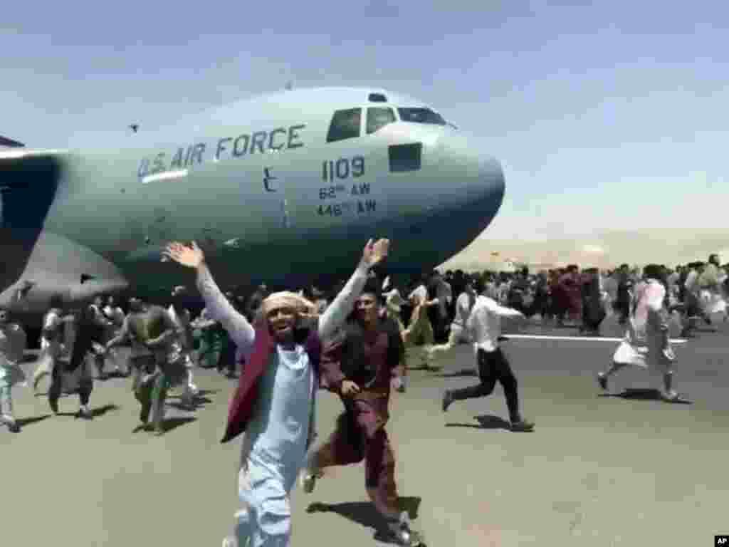 Стотици хора тичат покрай американски транспортен самолет, който се движи по пистата на международното летище в Кабул. В понеделник хиляди афганистанци се втурнаха на асфалта на международното летище в Кабул. В търсенето на отчаяни опити за бягство от страната, след като беше превзета от талибаните, някои от тях се хванаха самолета.