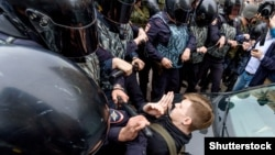 Russian police officers confront a teenager during a rally protesting hikes in the country's retirement age in St. Petersburg on September 9.