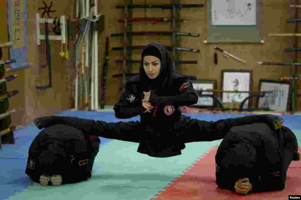 An Iranian woman performs a split as members of various ninjutsu schools showcase their skills to the media in a gym in Karaj, near Tehran. (Reuters/Caren Firouz)