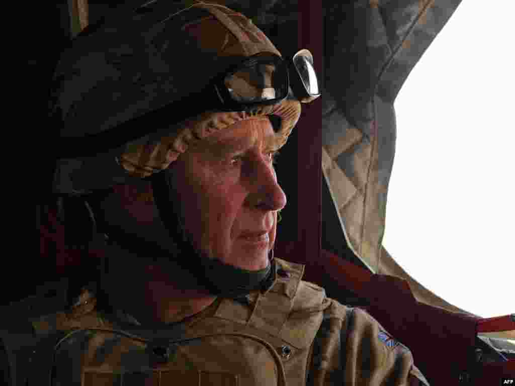 Britain's Prince Charles rides in a British military helicopter en route to Lashkar Gah, Afghanistan. - Prince Charles arrived in Afghanistan on March 25 on a surprise visit to meet with British soldiers serving in southern Helmand Province. Photo by AFP