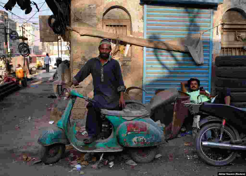 "A man poses with an old Vespa. A member of Lahore's Vespa fan club told Reuters ""Vespas were the second-best gift Italy gave to the world -- first being pizza."""