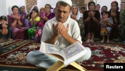Tajikistan -- The keeper of the Mausoleum of Muhammad Bashoro reads the Koran for his followers in the city of Panjakent, 12Aug2009