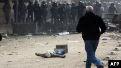 A man runs toward a wounded protester as security forces take position during clashes near the Interior Ministry in downtown Cairo on February 3.