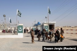 Pakistani soldiers keep guard as citizens return from Afghanistan at the border-crossing town of Chaman in October